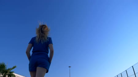 palma : Stylish blonde woman in a stylish denim overalls, walking along an empty street against the backdrop of palm trees. back view Stock Footage