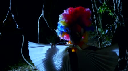 cicatrici : Halloween, clown malvagio con un fiocco al collo in una terribile foresta oscura di notte. lampi