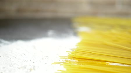 хрупкий : raw pasta cappellini, closeup lie in white flour on a wooden table