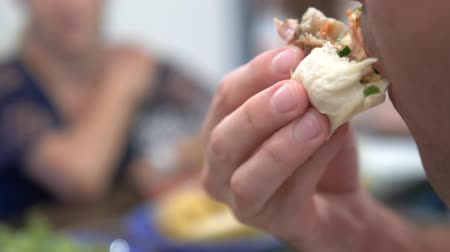 majonez : close-up. A man eats shawarma at home in the kitchen