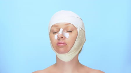 увеличение : The concept of plastic surgery. rhinoplasty, blepharoplasty, face lift. Portrait of a woman with a bandage on her head, nose and eyes. on blue background.