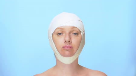 esvoaçantes : The concept of plastic surgery. face lift. Portrait of a woman with a bandage on his head, on a blue background.
