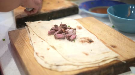 pita : hands close up. A man prepares shawarma on the kitchen table at home