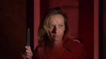 panico : A woman experiences fear and panic, walking along a dark corridor with a knife. Horror maniac concept. Halloween Filmati Stock