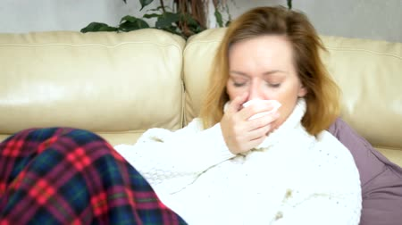 zsebkendő : Caucasian woman, with paper napkin sneezing, in a sweater under a blanket on the couch, experiencing allergy symptoms, caught a cold.