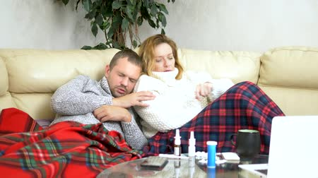 medical thermometer : concept of cold and flu virus, epidemic. husband and wife with fever lie on the living room sofa in sweaters and under blankets