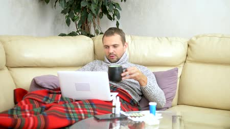 telemedicine : man with a cold sitting on the sofa in a sweater and a plaid calling his doctor on a laptop via video link. Stock Footage