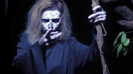 liaan : concept of horror, ghost woman in the forest. Beautiful woman with make-up skeleton in a scary forest.