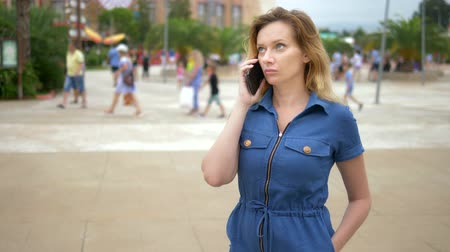 concerned girl : close-up. worried young woman talking on the phone. outdoor