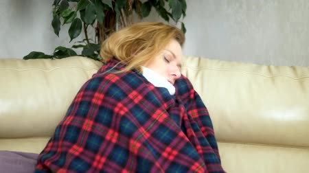 urlop : woman in a house on the sofa lying under a plaid at home suffering from cold and fever. The concept of cold and flu virus Wideo