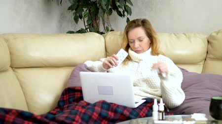 zsebkendő : blond woman with a cold sitting on the sofa in a sweater and a plaid calling her doctor on a laptop via video link. Medium shot