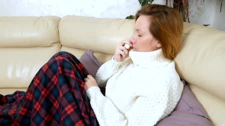 diseased : Beautiful woman with a runny nose uses a nasal spray at home, sitting on the sofa in the living room, in a sweater and under a blanket Stock Footage