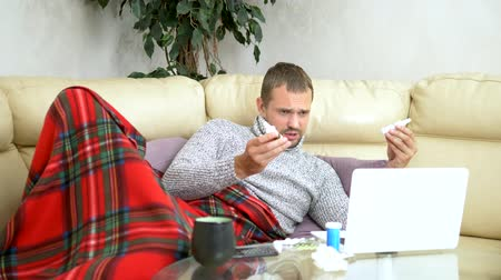 zsebkendő : man with a cold sitting on the sofa in a sweater and a plaid calling his doctor on a laptop via video link. Stock mozgókép