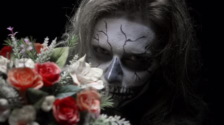 перелом : concept, beautiful makeup for halloween. Portrait of a young sexy girl with make-up of a skull and a bouquet of flowers.