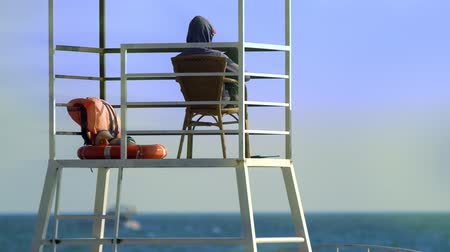 lifebuoy : Unrecognizable male lifeguard in a rescue tower on the beach. maritime safety concept Stock Footage