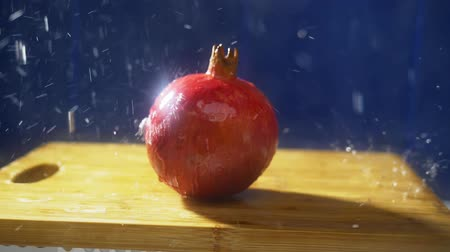 roma : Fresh pomegranates on a dark background in the studio under jets of rain. autumn harvest concept