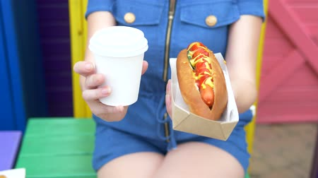 mustard : girl holds in her hand two delicious hot dogs on the street on a summer day