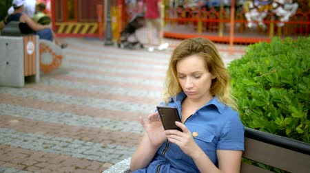 remotely : young woman uses smartphone at amusement park. Freelancer concept, works remotely Stock Footage
