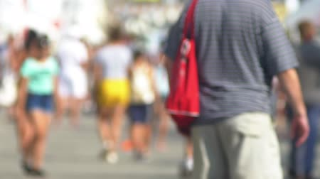 desfocado : blurred background. A crowd of unrecognizable people walking on a sunny summer day.