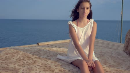 flooring : teenage girl in a white dress with long hair looks thoughtfully into the sea, being on a wooden terrace above the sea. wind develops hair