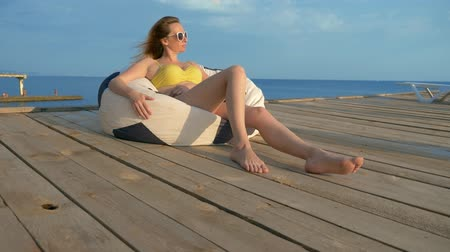 veranda : attractive young woman in a yellow swimsuit relaxes sitting in an armchair bag on a wooden veranda above the sea. Dostupné videozáznamy