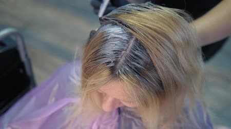 dyeing : close-up. hair dyeing concept. hairdresser colorist dye the hair of a woman with a brush Stock Footage