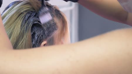 żel : close-up. hair dyeing concept. hairdresser colorist dye the hair of a woman with a brush Wideo