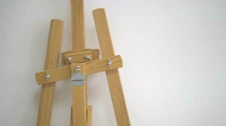 belirleme : Empty wooden easel , close-up against a white wall. Stok Video