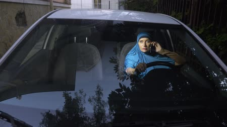steering wheel : view through the windshield of a car. Muslim woman in blue hijab talking on the phone while driving a car. Stock Footage