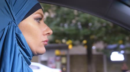 きちんとした : close-up. beautiful muslim woman in blue hijab driving a car. rides during the day on the streets of the city. 動画素材
