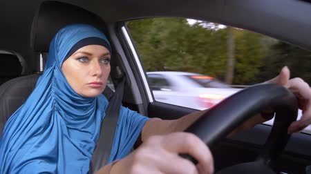 yönlendirmek : beautiful muslim woman in blue hijab driving a car. rides during the day on the streets of the city.