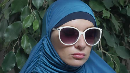 ficus : portrait of a beautiful muslim caucasian woman wearing sunglasses on a background of ficus foliage
