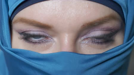 экзотичность : close-up. beautiful blue eyes of arab young woma in traditional islamic cloth niqab Стоковые видеозаписи