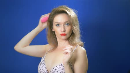 болваны : pin-up girl concept. Pin-up woman straightens her hair, looking at the camera, blue background. copy space Стоковые видеозаписи