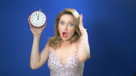 pinup : Surprised pin-up woman holding clock. Amazed pinup girl. Saving time concept. Summer sale. Discount. blue background Copy space. Expressive facial expressions. Stock Footage