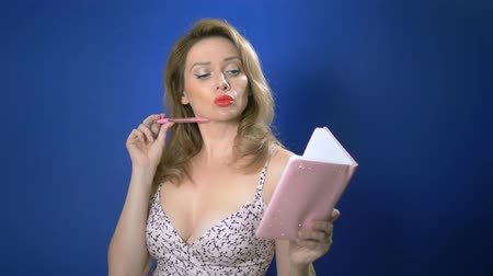 roman : Pinup girl with a pink notebook and pen. thinks what to write in a notebook. Retro style . romance love, positive emotions. blue background, copy space Stok Video