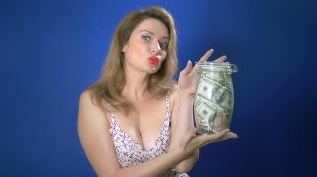 retro revival : money saving concept. pin-up woman holding a glass jar filled with dollars on a blue background. adventures of strange people. copy space Stock Footage