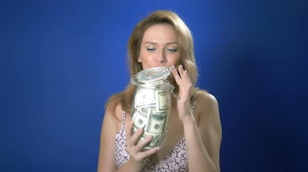 pinup : money saving concept. pin-up woman holding a glass jar filled with dollars on a blue background. adventures of strange people. copy space Stock Footage