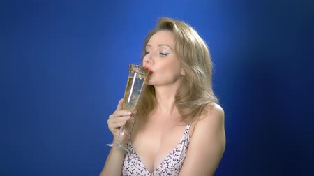 pinup : charming girl with retro make-up holds a glass of champagne. concept of congratulations, wishes for a happy holiday. blue background, copy space Stock Footage