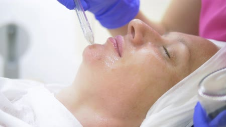 tlen : cosmetology concept, face care. woman face during the procedure of jet peeling, facial
