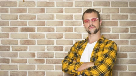 finom : handsome young man in a yellow checkered shirt and pink glasses, pointing to a place for text, a place for advertising Stock mozgókép