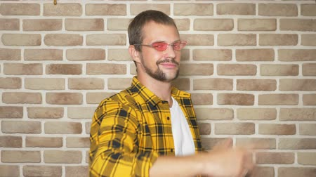 урод : come to me . a cool bearded man in pink glasses and a fashionable yellow checkered shirt, pulling his hands to the camera, inviting his comrades to go inside, greeting the guest at the party. against a brick wall Стоковые видеозаписи