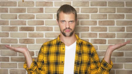 tartmak : handsome man in a fashionable yellow plaid shirt compares, options for weights, against a brick wall