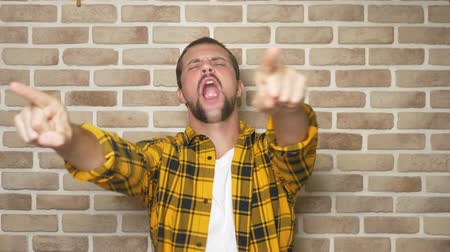 erledigt : happy handsome man in a plaid shirt celebrates victory with victory gesture on a brick wall background.
