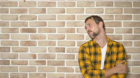 odd eyed : upset handsome man in a fashionably yellow checkered shirt against a brick wall, copy space. gestures and emotions concept