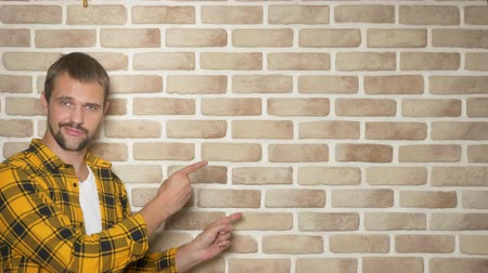 хороший : handsome young man in a yellow checkered shirt, pointing to a place for text, a place for advertising
