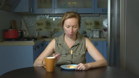 descontente : diet concept, tasteless food. Frustrated and annoyed woman eating food from a plate and disappointed