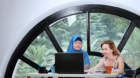 многонациональная : multinational team concept. Two women, a Muslim woman in a hijab and a Caucasian woman in an open top, work together at the office using a laptop.