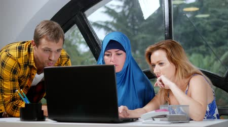 kelet európa : multinational team concept. muslim woman in hijab, caucasian woman and caucasian man working together in the office using laptop.
