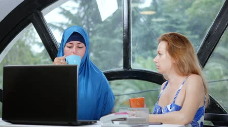 kelet európa : multinational team concept. Two women, a Muslim woman in a hijab and a Caucasian woman in an open top, work together at the office using a laptop.